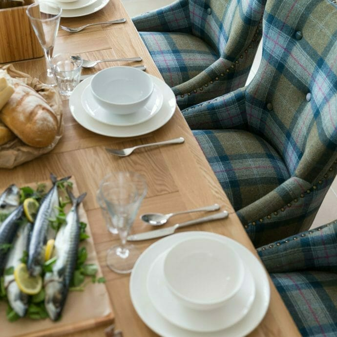 Wooden dining table with green and blue plaid chairs by Camellia