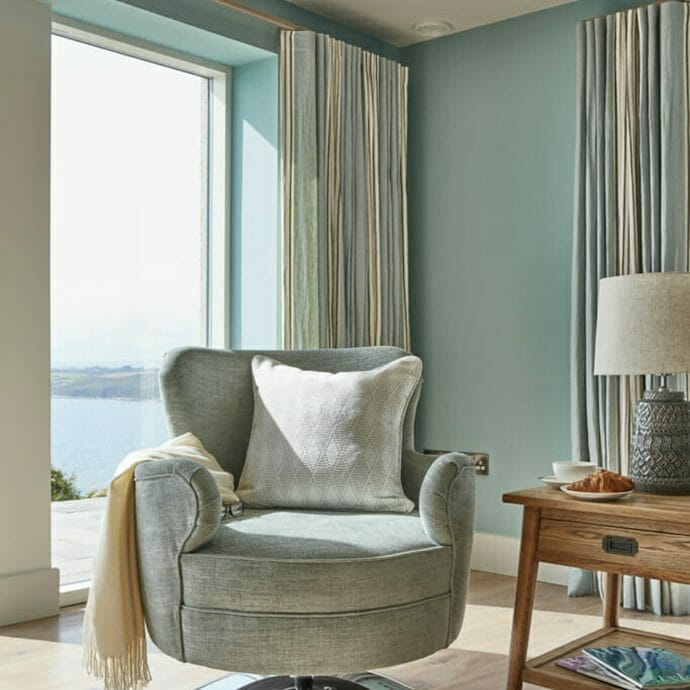 Bespoke Aqua blue swivel chair with made to measure curtains in Romo fabric.